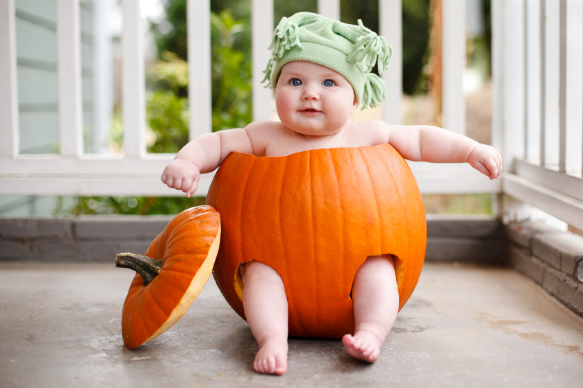 Baby sitting in a pumpkin